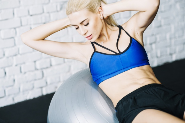 woman-doing-abs-exercises-on-fitball_23-2147687872
