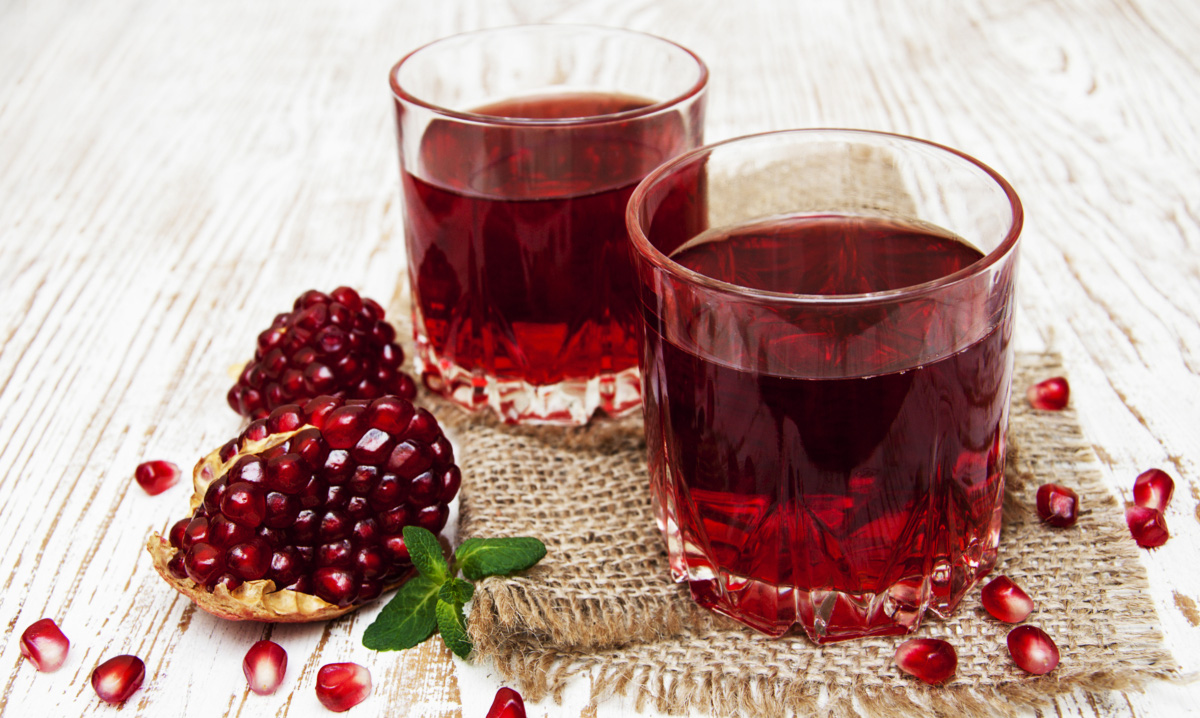 Two glasses of pomegranate juice with fresh fruits on wooden table